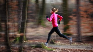 Young woman running outdoors in a city park on a cold fall/winte